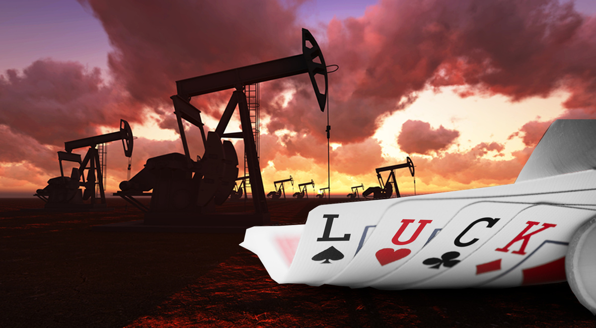 Poker cards with the letters L, U, C, K written on them in front of an oil field pump jacks at sunset