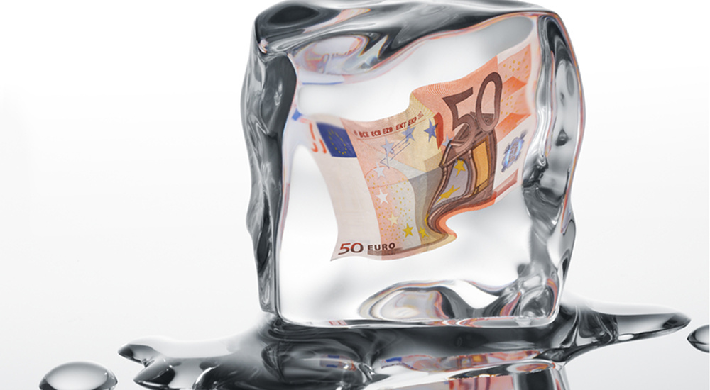 Euro banknote frozen in ice cube - financial crisis concept